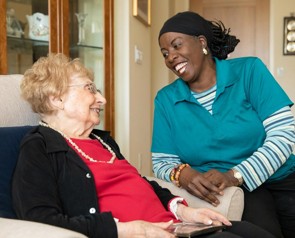 Photo of a Caring Friends employee laughing with a senior client.
